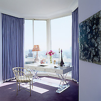In the master bedroom a large floor-to ceiling bay window affords panoramic views over Manhattan