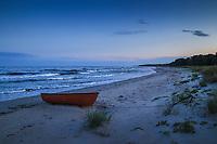 Båt på sandstrand i skymning över havet Östelen Skåne