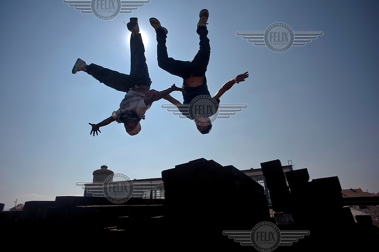 Two teenagers perform 'Salti' (jumps) in the rail yard at Fushe Kosova/Kosovo Polje.