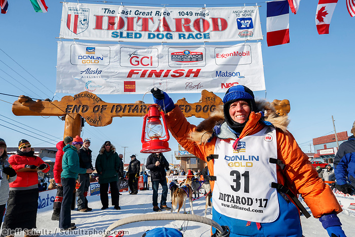 Last place finisher and Red Lantern Award winner Cindy Abbott holds up the red lantern after her finish in Nome during the 2017 Iditarod on Saturday March 18, 2017.<br /> <br /> Photo by Jeff Schultz/SchultzPhoto.com  (C) 2017  ALL RIGHTS RESERVED