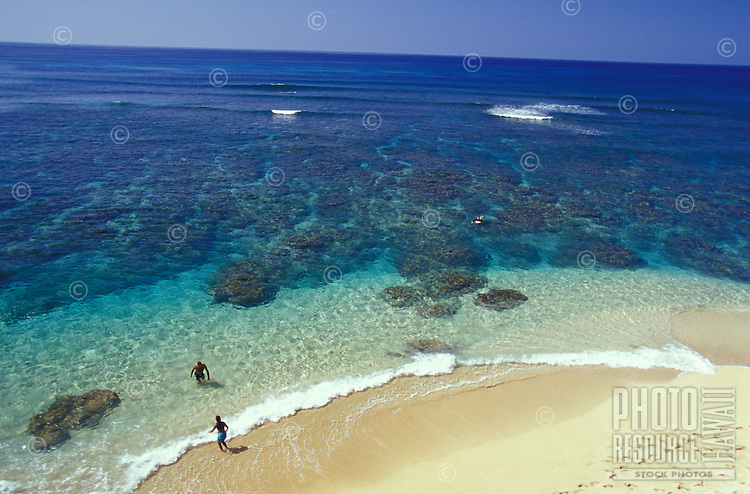 People playing on white sand beach and in clear water on Hideaways Beach, Kauai