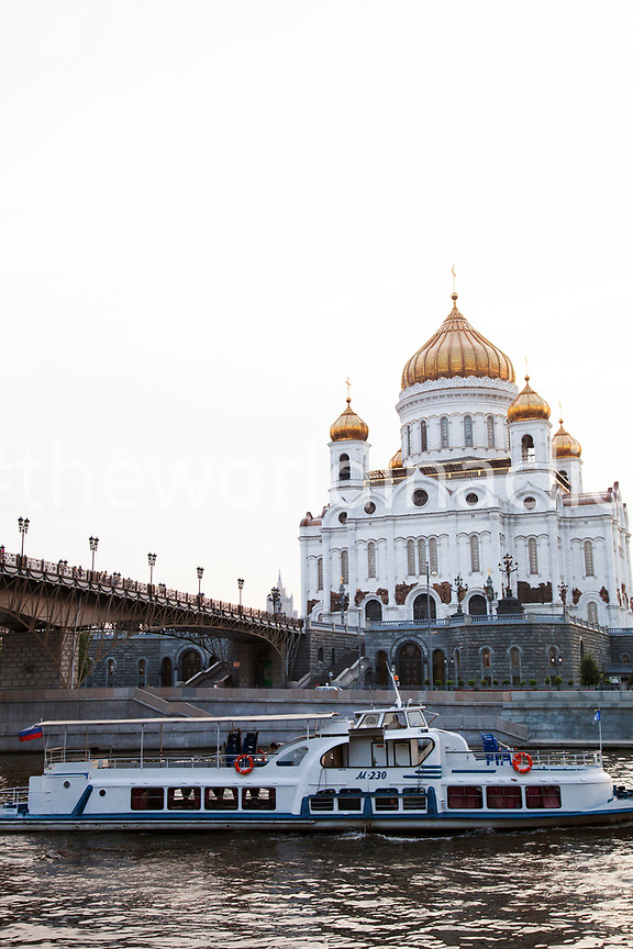 RUSSIA, Moscow. A ferry passes under the Patriarshy Bridge on the Moscow River with the Cathedral of Christ the Saviour in the background.