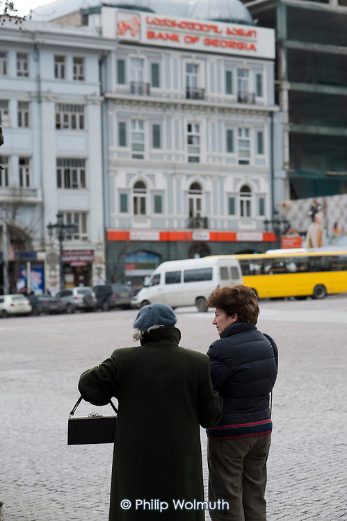 Two women wait for a bus opposite the Bank of Georgia in Freedom Square, Tbilisi.