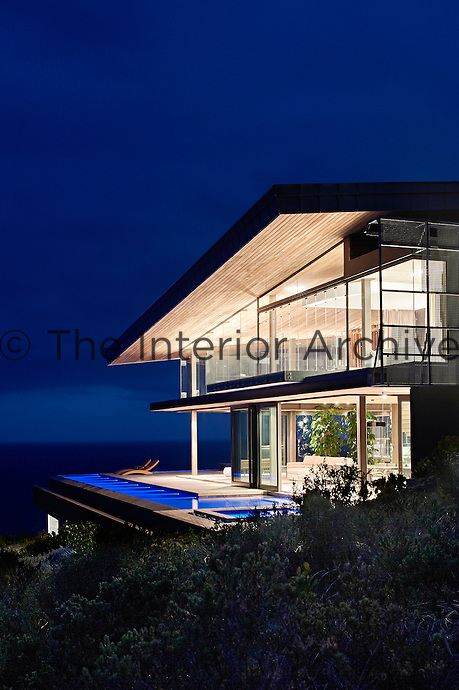 """Lighting at night is subdued. """"We wanted to push light up onto the roof so that all the surfaces are lit rather than the air. You can put less light into the space if do that,"""" says lead architect Greg Truen.  An extensive home automation system controls the lighting and background music.<br /> <br /> When the folding doors are stacked away the sloping roof seems to float in space, a glittering jewel on the cliff."""
