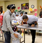 United States President Barack Obama talks with a young customer as he packs and delivers bags of food to area residents Martha's Table on Wednesday, November 24, 2010, in Washington, DC.  .Credit: Leslie E. Kossoff - Pool via CNP