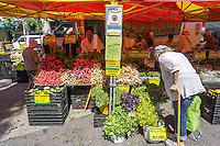 A elderly woman shop for produce at the Union Square Greenmarket in New York on Saturday, July 16, 2016.  (© Richard B. Levine)