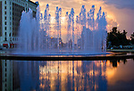 The fountain in front of Union Station, in Kansas City, sprays water into the sky as the sun begins to set.You can see reflections of the spraying water in the clear pool and buildings in the background.
