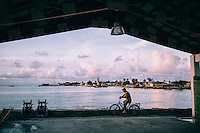 A man on a bicycle waits at the Ebeye ferry terminal for the passenger boat to come from nearby Kwajalein Island.