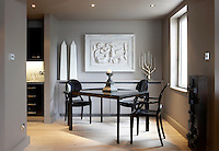 Three black Philippe Starck Ghost Chairs are placed around a table in the dining area at one end of the kitchen