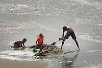 Nederland, Vrouwenpolder, 15 aug 2007..Zandkastelen. Op de vloedlijn van een strand in Zeeland vechten kinderen met vaders tegen het water dat hun zandkasteel bedreigt. Familie bezigheden aan het strand.  Met scheppen en emmertjes wordt nog zand aangebracht. Vloed. Golven. .Associatie zeespiegelstijging.Foto (c) Michiel Wijnbergh.