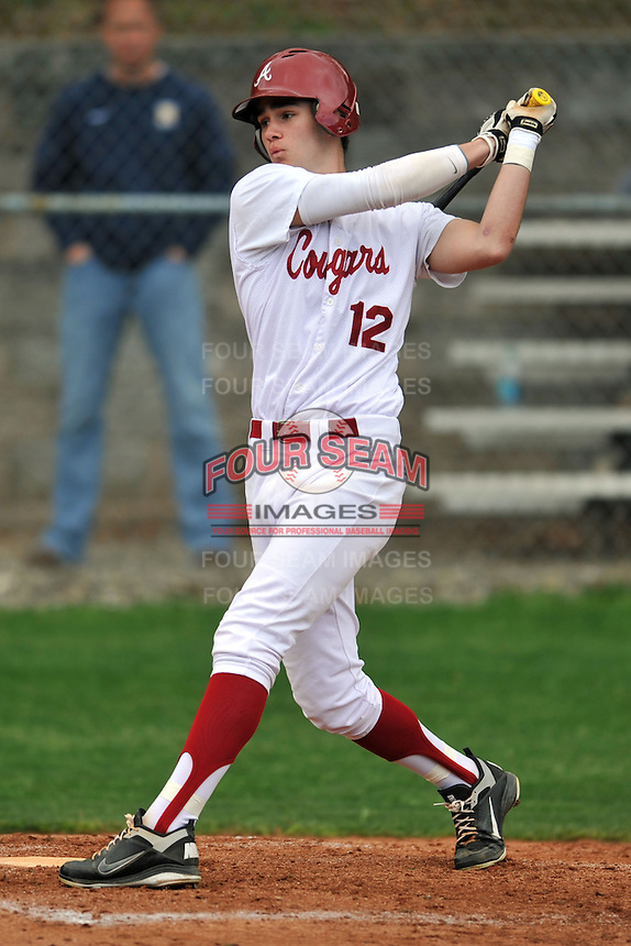 Asheville Cougars left fielder Miles Moore #12 swings at a pitch during a game against the T.C. Roberson Rams  at Asheville High on April 15, 2013 in Asheville, North Carolina. The Rams won 4-1. (Tony Farlow/Four Seam Images).