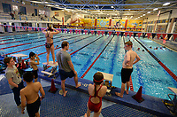 Dawson Layman, head development coach for the AquaHawgs swim team, speaks to swimmers Thursday, Jan. 9, 2020, as they begin swimming laps during practice at the Jones Center in Springdale. About 120 members of the team practice at the pool in three shifts because of a lack of indoor public pools in Northwest Arkansas. Check out nwaonline.com/200112Daily/ for today's photo gallery.<br /> (NWA Democrat-Gazette/Andy Shupe)