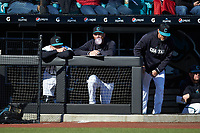 Coastal Carolina Chanticleers student assistant Matt Heidenreich (center) blows a bubble as he watches from the dugout during the game against the Illinois Fighting Illini at Springs Brooks Stadium on February 22, 2020 in Conway, South Carolina. The Fighting Illini defeated the Chanticleers 5-2. (Brian Westerholt/Four Seam Images)