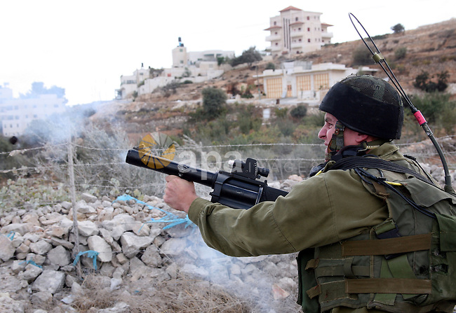 An Israeli soldier fires tear gas during a protest against the controversial Israeli barrier in the West Bank village of al-Masarah, near Bethlehem, October 29, 2010. Israel says the barrier is needed for security, but Palestinians think of it as a land grab that undermines their promised state. Photo by Najeh Hashlamoun