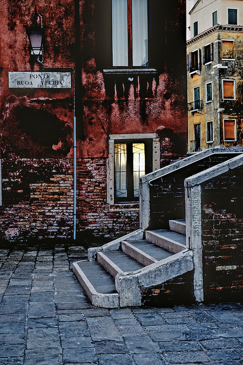A warm glow comes from a window in Venice, Italy. Just nearby are stone steps over a canal.