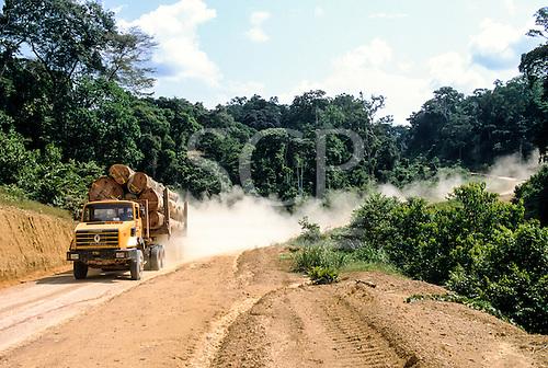 La Gongue, Gabon. Renault trucks loaded with Okume tree trunks on a dirt road.