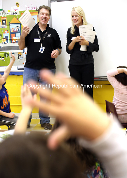 BEACON FALLS CT. 20 November 2015-112015SV03-Lewis and Annette Boyce of Beacon Falls play a job and careers game with students during a donut production exercise for a Junior Achievement lesson at Laurel Ledge Elementary School in Beacon Friday. It was Junior Achievement day at the school.<br /> Steven Valenti Republican-American