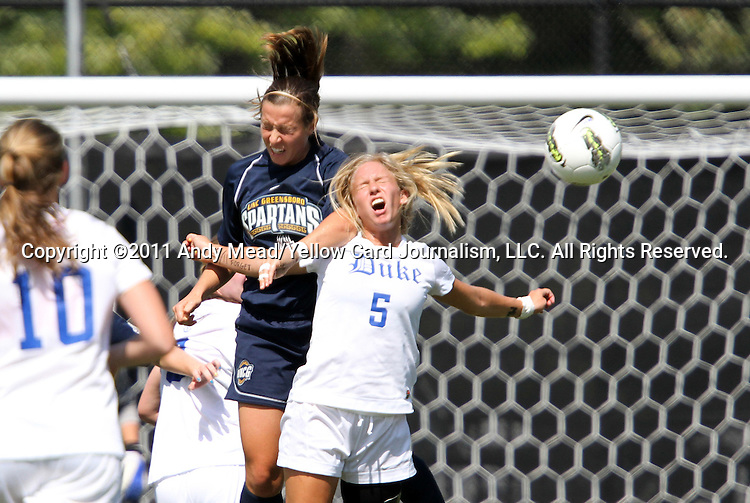 11 September 2011: Duke's Kaitlyn Kerr (5) gets an elbow in the neck on a challenge from UNCG's Jaimy Etten (behind). The Duke University Blue Devils defeated the University of North Carolina at Greensboro Spartans 2-0 at Koskinen Stadium in Durham, North Carolina in an NCAA Division I Women's Soccer game.