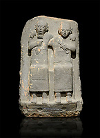 Hittite monumental relief sculpture of of two seated figure, not a typical Hittite style with a lot of other influences. Late Hittite Period - 900-700 BC. Adana Archaeology Museum, Turkey. Against a black background