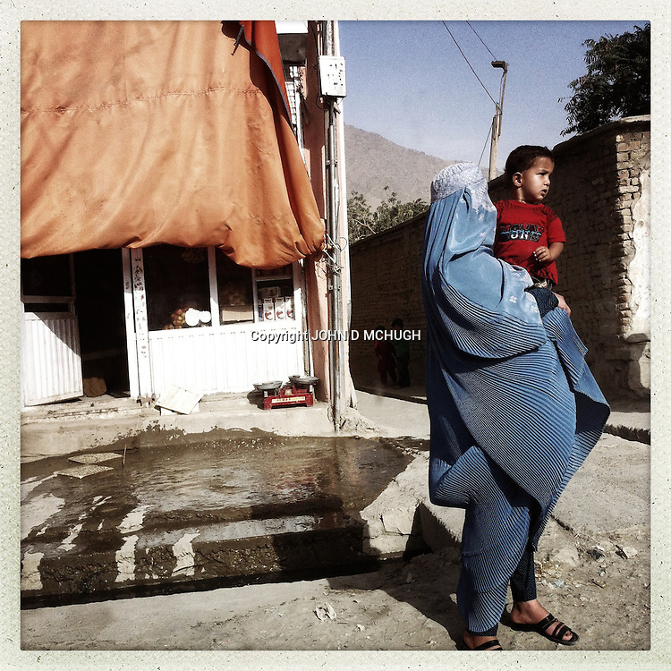 ** TO GO WITH AFGHANISTAN STORY FOR PETER MURTAGH - NO ARCHIVE, NO RESALE ** A woman and child are seen on the street in Kabul, 28 August 2012. (John D McHugh)