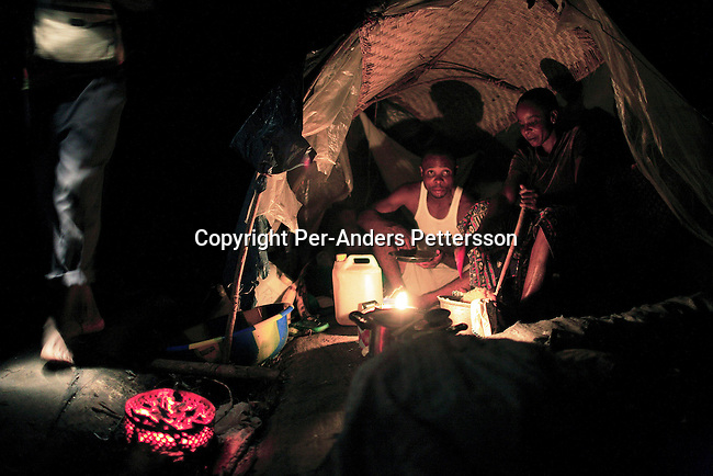 MBANDAKA, DEMOCRATIC REPUBLIC OF CONGO JUNE 26: Unidentified passengers cook beans and rice in their hut, while traveling on a boat made of big trees on the Congo River on June 26, 2006 outside Mbandaka, Congo, DRC. The boat traveled with about 150 passengers from Bumba to Kinshasa, a journey of about 1300 kilometers. The Congo River is a lifeline for millions of people, who depend on it for transport and trade. Passengers slept in the open, with their goats, pigs and other animals. Boat travel is the only option for most people along the river as there?s no roads or infrastructure. Very few can afford to fly in a plane to the capital Kinshasa. During the Mobuto era, big boats run by the state company ONATRA dominated the river. These boats had cabins and restaurants etc. All the boats are now private and are mainly barges that transport goods. The crews sell tickets to passengers who travel in very bad conditions. The conditions on the boats often resemble conditions in a refugee camp. Congo is planning to hold general elections by July 2006, the first democratic elections in forty years. The Congolese and the international community are hoping that Congo will finally have piece and the country will be rebuilt. (Photo by Per-Anders Pettersson).