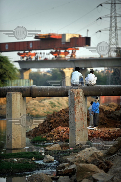 Children sit on a pipeline near a major road being built in preparation for the 2010 Commonwealth Games.