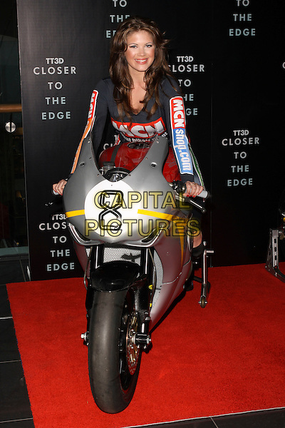 "GEORGINA TERRANA.The ""TT3D: Closer To The Edge"" UK Premiere, Westfield, London, England, UK, 14th April 2011.full length sitting blue catsuit motorbike motorcycle .CAP/AH.©Adam Houghton/Capital Pictures."