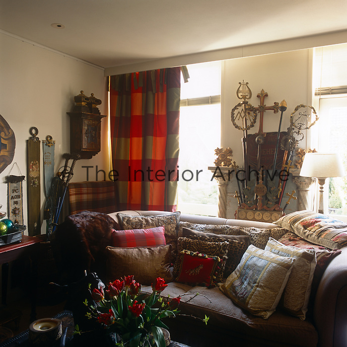 A traditional sitting room with a sofa piled with cushions. A red checked curtain hangs at the window next to a collection of crosiers and staffs.