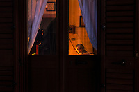 Italy. Apulia Region. Ceglie Messapica. An elderly woman seats alone at home and watches television in the night time. Ceglie Messapica is a town and comune located in Apulia (Puglia), a region in Southern Italy. 6.12.18  © 2018 Didier Ruef