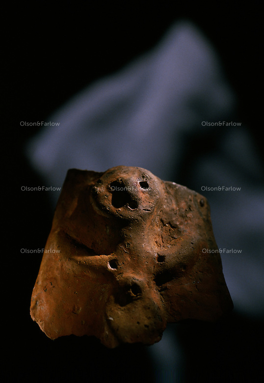 A close view of a Bronze Age mother-goddess figurine made of clay.
