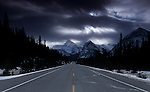 The highway vanishes in the distance where beams of light shine through distant storm clouds along the Icefields Parkway in Alberta Canada.