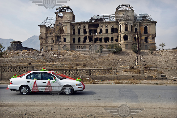 A wedding car passes the ruins of the Darul Amun Palace.