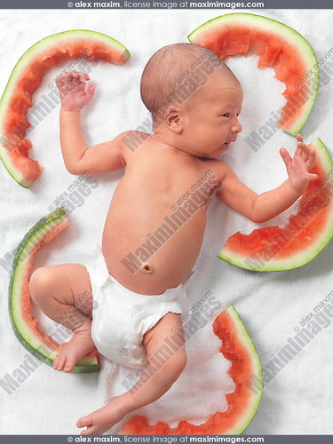 Newborn baby in a diaper lying down amongst watermelon rinds after a good meal