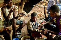 Farm labourers at Lucien Kro camp eat a meal in a forest shelter.