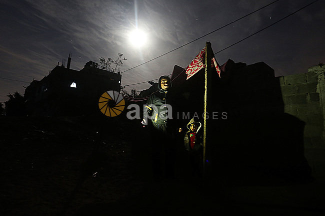 Palestinians stand outside their house during the power outage on winter season in the Jabalia refugee camp in the northern of Gaza Strip on January 11, 2017. Power shortages in the Palestinian enclave have occurred repeatedly in recent weeks, with homes in Gaza City typically getting around four hours a day - rather than at least eight normally. The roughly two million people in Gaza rely on one power plant, as well as imports from Israel and Egypt. Photo by Yasser Qudih