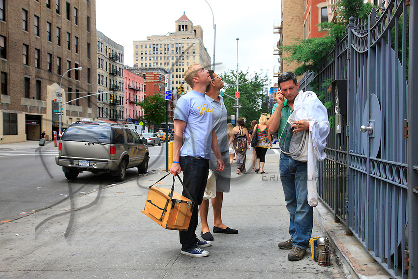 "Andrew Coté, beekeeper, Adam Johnson, a beginner and Troy Seidman, a curious friend, with their beekeeping material in front of a building with an apiary in the East Village. Adam says, ""It was an old desire, from childhood, but when CCD started in the United States, I really wanted to have beehives and start beekeeping. I have one hive and I take care of 4 others with Andrew in a community garden in the East Village."""
