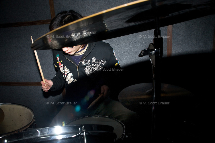 Du Wei, drummer for the Chinese punk band Overdose, plays in a small practice space late at night in the backroom of a tattoo parlor in Nanjing, China.