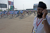 Race security official signals that riders have passed fist the UCI circuit's first U-turn - 2010 Tour of Mumbai Cyclothon - India