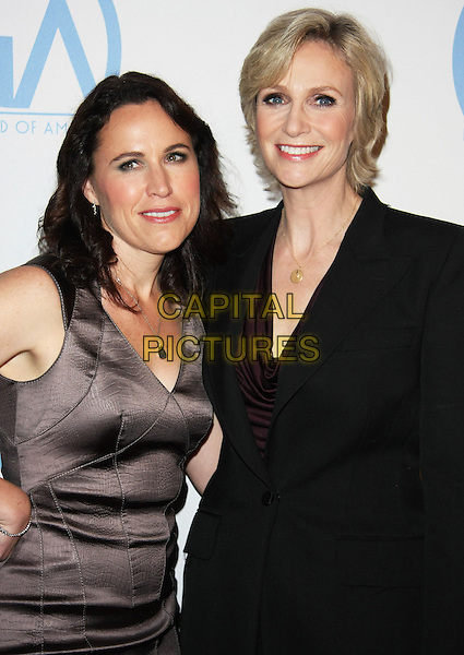 DR. LARA EMBRY & JANE LYNCH .22nd Annual Producers Guild Awards held at The Beverly Hilton, Beverly Hills, California, USA, 22nd January 2011..half length black suit jacket  brown dress couple .CAP/ADM/TB.©Tommaso Boddi/AdMedia/Capital Pictures.