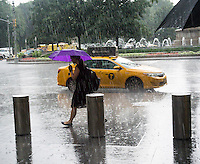 Pedestrians break out their umbrellas or run between the rain drops during a storm outside the Time Warner Center in New York on Thursday, July 30, 2015. Storms are expected to douse the city this afternoon prompting flash flood and thunderstorm warnings. (© Richard B. Levine)