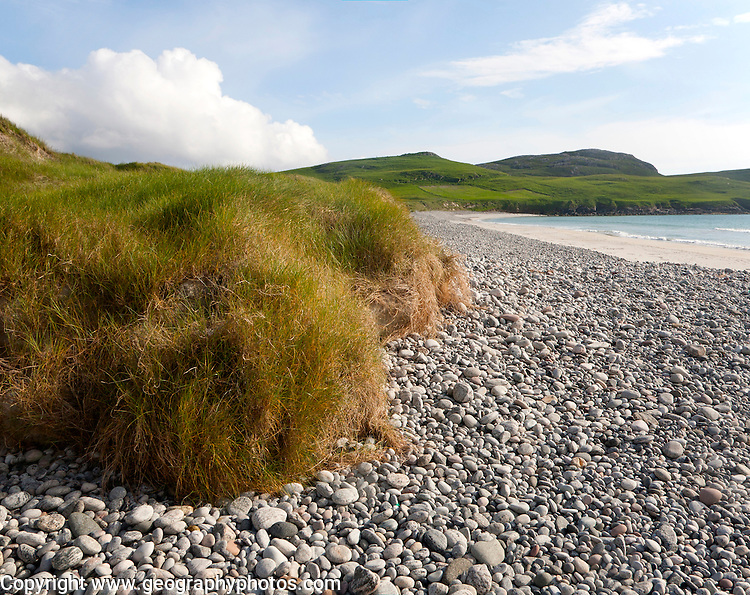 Low angle view of pebbles, sandy beach and dune vegetation on Traigh Siar beach, Vatersay, Barra, Outer Hebrides, Scotland, UK