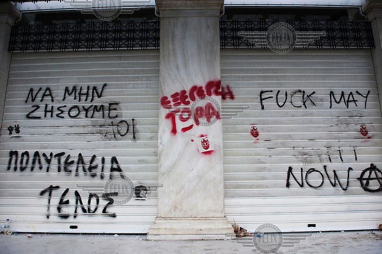 Graffiti on the facade of King George Hotel in Syntagma Square in Athens. It reads 'We shouldn't leave as slaves, the end of luxury and the revolution is happening now'. Extensive rioting took place in Athens on the day austerity measures were passed by the government, as the country tries to recover from it's severe financial crisis. Future funding for Greece from the EU and IMF was made conditional on a positive response from the vote.
