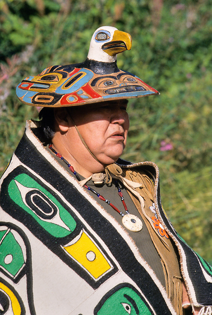 Tlingit man dressed in traditional chilkat blanket and carved wooden eagle hat with brim headdress attends a totem pole raising ceremony, Anchorage Alaska