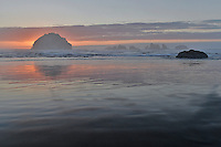 Face Rock with Cat & Kittens sea stack rock formations silhouetted by a setting sun offshore Bandon Beach, OR. at low tide.
