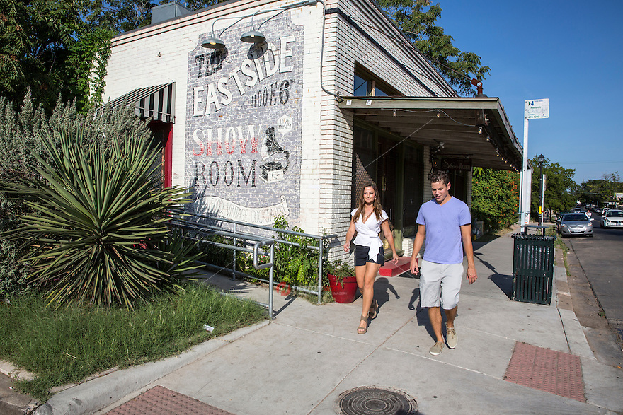 Couple walks around the revitalized East Sixth Street, also known as the Eastside in East Austin on a hot summer's day Austin, Texas.