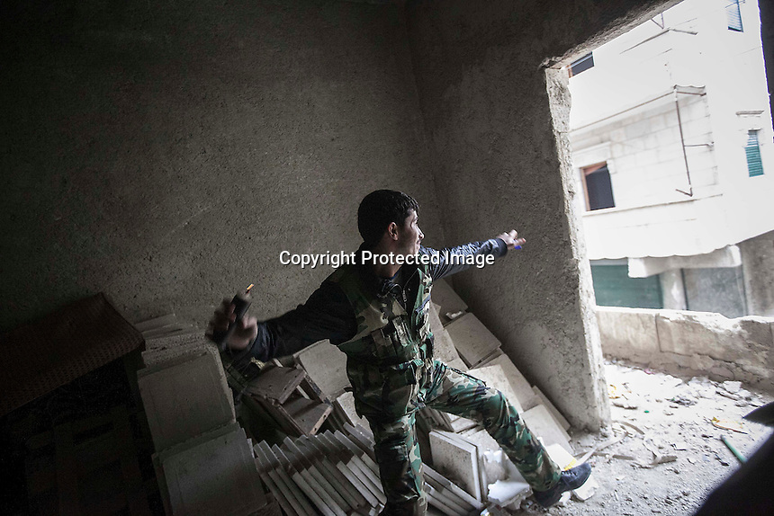 In this Friday, Dec. 07, 2012 photo, a rebel fighter throws a grenade toward Syrian troops loyal to President Bashar al-Assad during clashes in Aleppo, Syria, Friday. (AP Photo/Narciso Contreras)