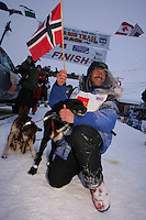 """Robert Sorlie poses with one of his lead dogs """"Sox"""" shorlty after winning the 2005 Iditarod at the finish line in Nome.  End of the  2005 Iditarod Trail Sled Dog Race."""