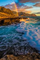 A colorful rainbow over the Wai'anae Mountains, with waves crashing over the rugged coastline near K'aena Point, O'ahu.