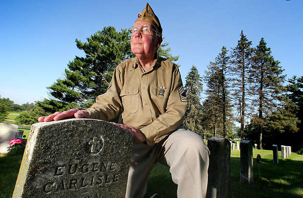 Gerald LeBlanc, a tireless advocate for the maintenance and repair of veterans' headstones, kneels with a row of aging Worls War I grave markers at Glendale Cemetery on June 30 in Des Moines.