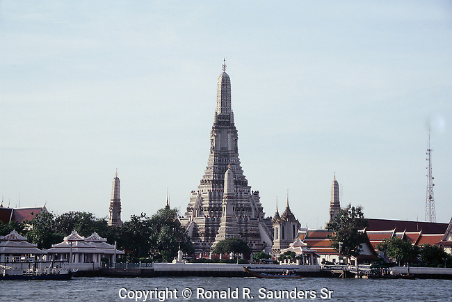 Wat Arun Ratchawararam Ratchawaramahawihan or Wat Arun is a Buddhist temple in Bangkok Yai district of Bangkok, Thailand, on the Thonburi west bank of the Chao Phraya River. The temple derives its name from the Hindu god Aruna, often personified as the radiations of the rising sun. Wat Arun is among the best known of Thailand's landmarks and the first light of the morning reflects off the surface of the temple with pearly iridescence. Although the temple had existed since at least the seventeenth century, its distinctive prang were built in the early nineteenth century during the reign of King Rama II.
